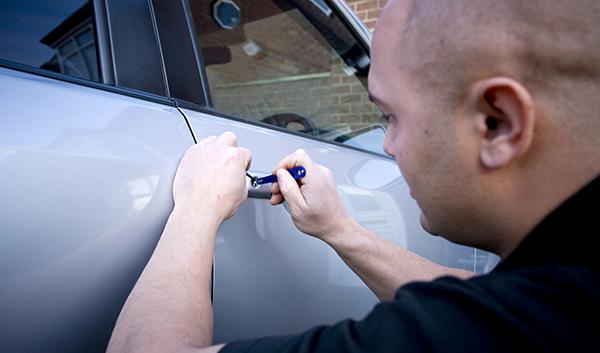 Emergency auto Locksmiths opening a car